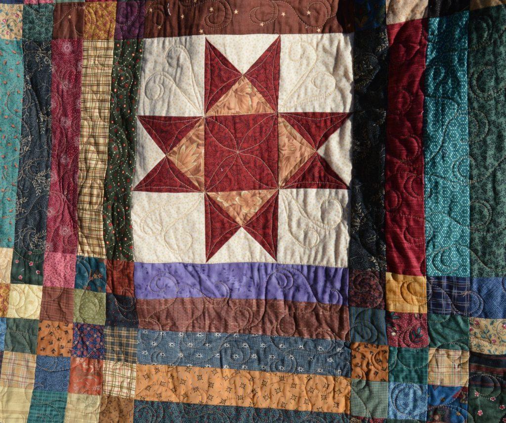 machine quilting design on scrappy ohio star quilt