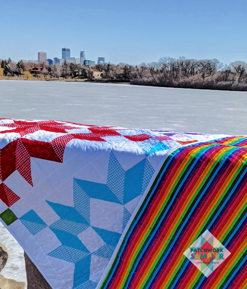 Rainbow stripe fabric on back of carpenter's star quilt